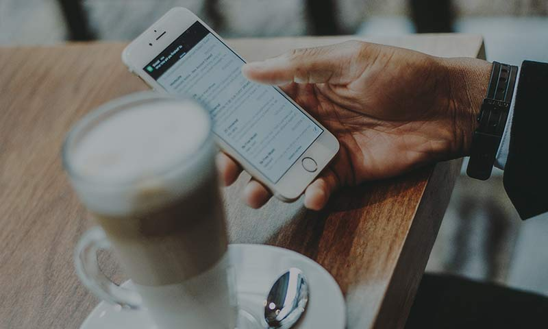 Man med telefon och kaffe